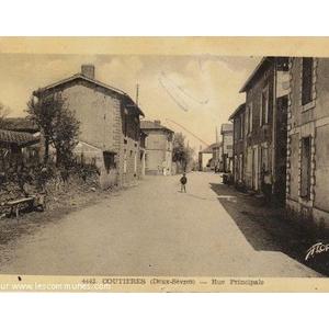 Carte postale ancienne  montrant la rue principale , on appercoit une borne Michelin à la croisée des rues